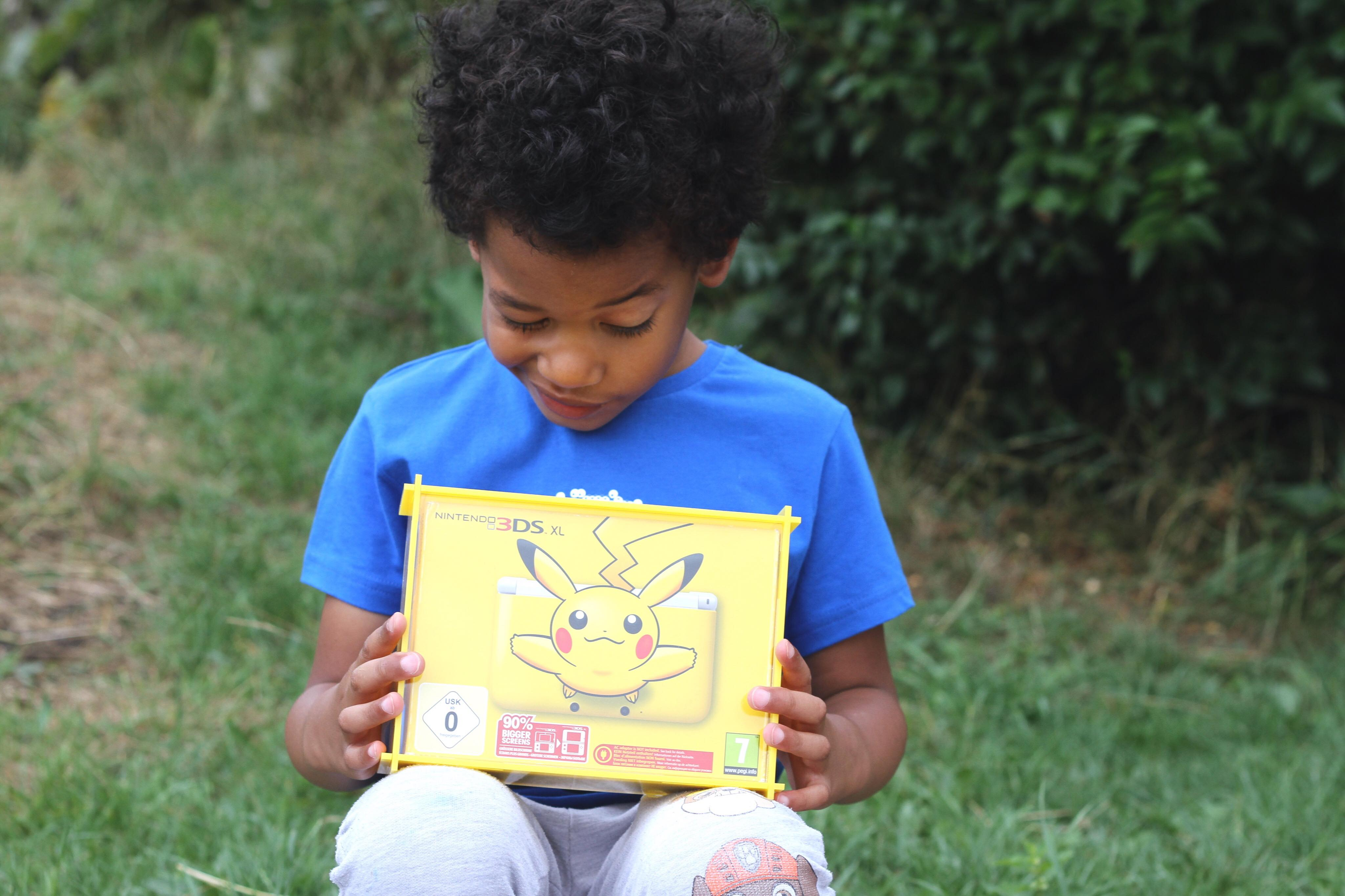 Young boy holding a yellow display case for a Pokemon Nintendo 3DS XL box